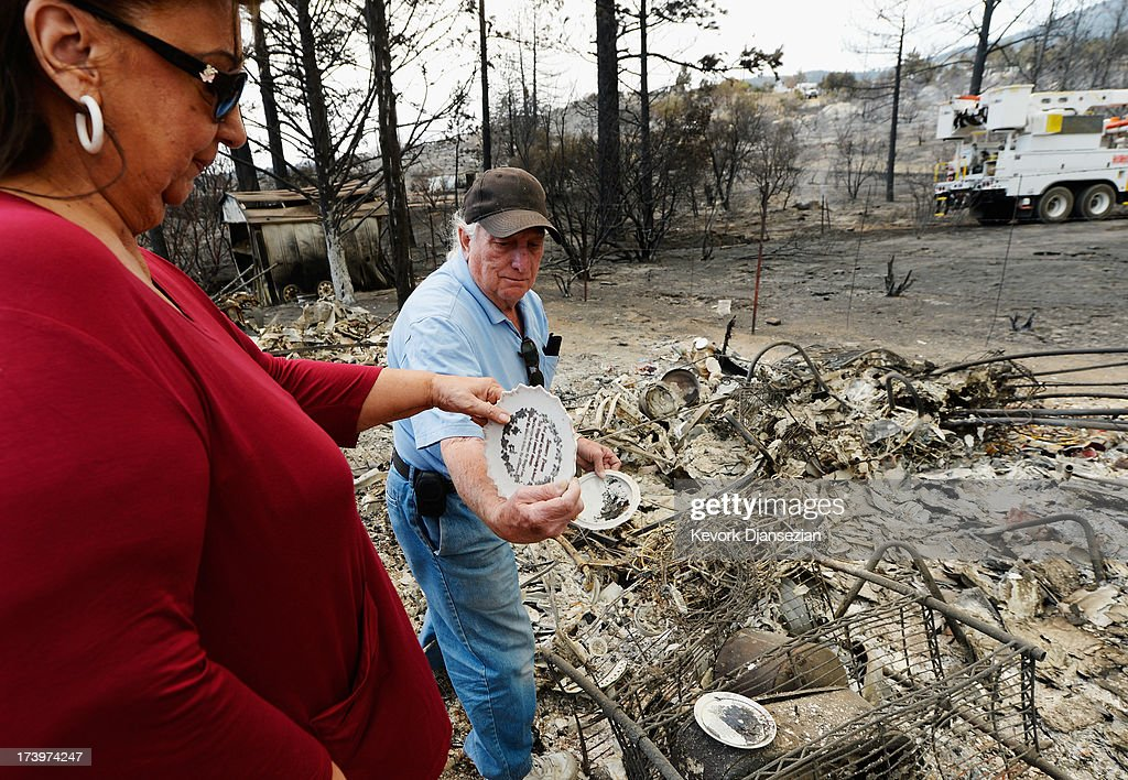 Lucille Prevosto and her husband Joe Prevosto look through charred remains of a storage shed where they stored their furniture, china and personal memrobilia on their son's Marty Prevosto's property, which was destroyed by the Mountian Fire July 18, 2013 near Idyllwild, California. The massive wildfire in Riverside county has grown to 23,000 acres and is advancing towards the mountain town of Idyllwild on one front and city of Palm Springs on the other front destroying several homs and forcing the evacuation of 6,000 people.