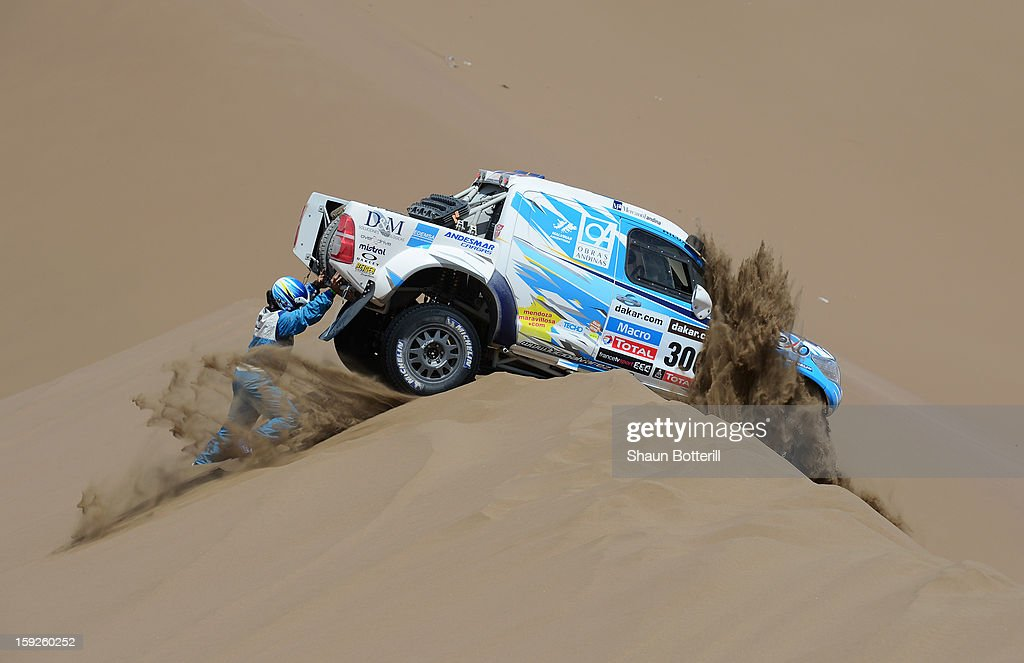 Lucio Alvarez and co-driver Ronnie Graue of team Toyota try to move their stranded car during stage 6 from Arica to Calama during the 2013 Dakar Rally on January 10, 2013 in Arica, Chile.