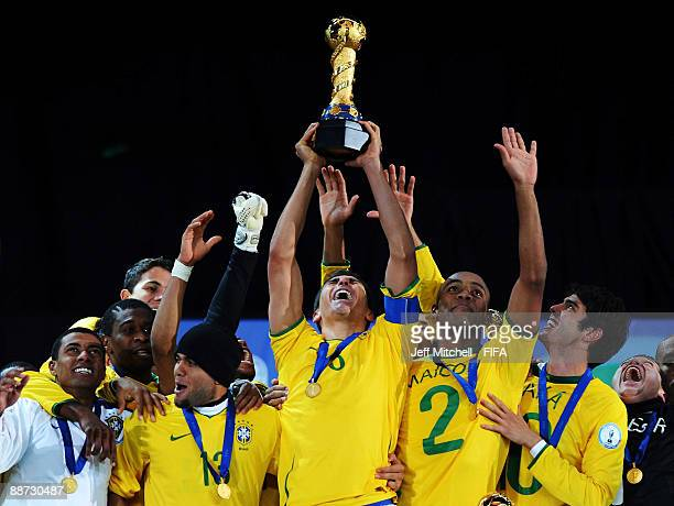 Lucio of Brazil lifts the trophy as his team mates celebrate following their victory at the end of the FIFA Confederations Cup Final between USA and...