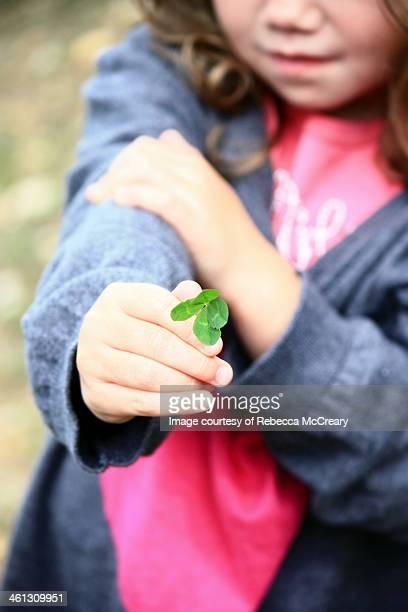 Lucky girl, child holding four leaf clover