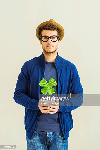 Lucky hipster holding four leave clover