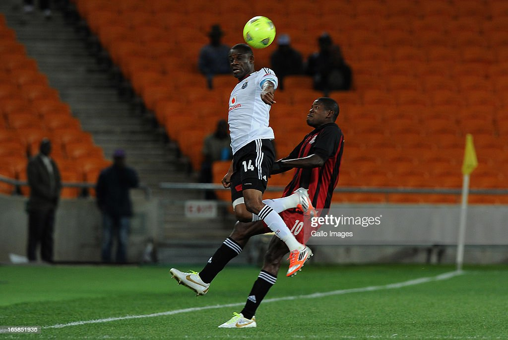 Lucky Lekgwathi of Pirates battling for the ball with Dawies Mwape of Zanaco FC during the CAF Confedaration Cup match between Orlando Pirates and Zanaco at FNB Stadium on April 06, 2013 in Johannesburg, South Africa.