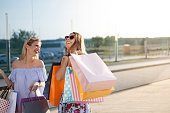 Two beautiful girls are shopping. they are located in the shopping center. They are very happy.