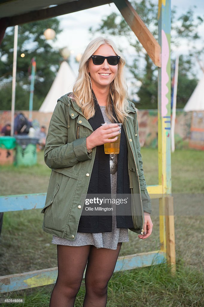 Lucy 22, an interior designer from Sussex wearing a dress from H&M, Jacket coat and necklace from Topshop, wellies by Hunter and Sunglassses by Ray Ban on the last day of the Glastonbury Festival at Worthy Farm on June 29, 2014 in Glastonbury, England.