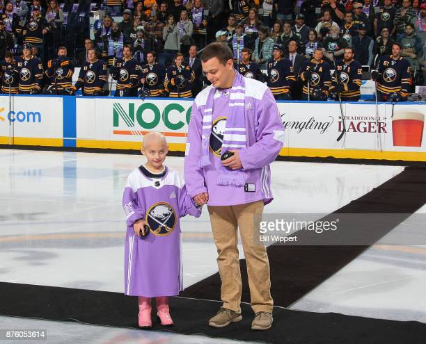 Lucy and Cameron take part in pregame ceremonies on Hockey Fights Cancer Night before an NHL game between the Buffalo Sabres and the Carolina...