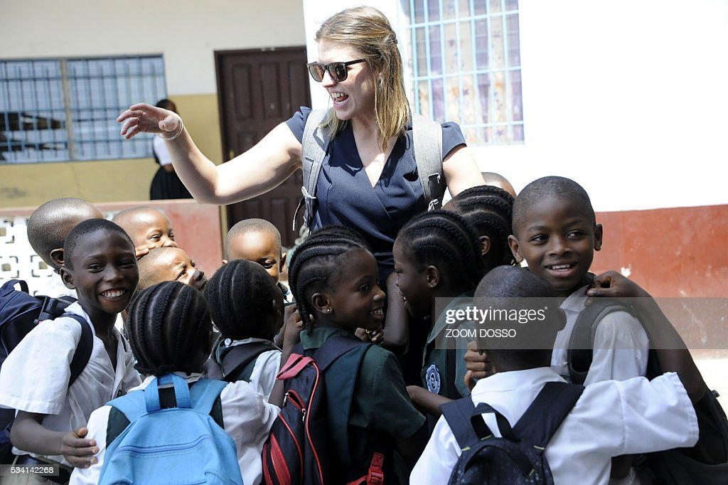 Lucy Bradlord from Bridge International Academies chain (C) chats with pupils in Monrovia on May 25, 2016. For the new school year, the Liberian government plans to roll out a public-private partnership involving 120 primary schools, costing an initial $65 million -- the equivalent of more than three quarters of the entire education budget. / AFP / ZOOM