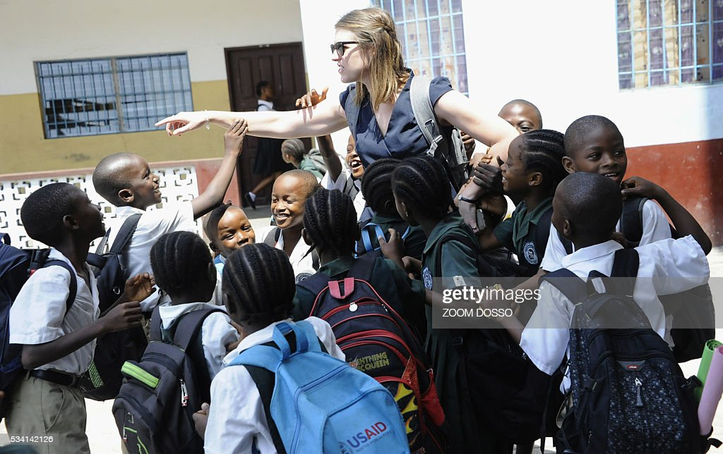 Lucy Bradlord from Bridge Internationals (C) chats with pupils in Monrovia on May 25, 2016. For the new school year, the Liberian government plans to roll out a public-private partnership involving 120 primary schools, costing an initial $65 million -- the equivalent of more than three quarters of the entire education budget. / AFP / ZOOM