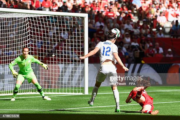 Lucy Bronze of England heads her team's winning goal past Erin McLeod of Canada during the FIFA Women's World Cup 2015 Quarter Final match between...