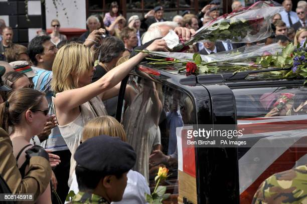 Lucy Chittended partner of Major Josh Bowman places a small bunch of red roses on top of the hearse containing the Union Flag draped coffin of her...
