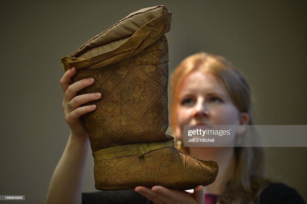 Lucy Clarke of Bonham's, holds a 12th century silk boot at an Islamic Art Exhibition at Bonham's on January 7, 2013 in Edinburgh, Scotland. The private collection of Islamic Art is due to be exhibited from January 8 - 13th at Bonham's in Edinburgh. This collection has never been seen in public before and is Scotland's largest private and internationally important collection of Islamic art including over 650 items from pre-Islamic and Islamic culture. Primarily featuring objects from the Land of Timur, Central Asia; those on display are ancient ceramics, bronzes, books, goblets, glass, furniture, paintings, textiles and coins.