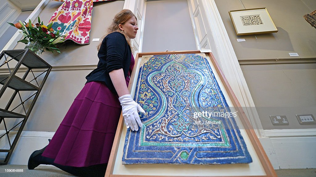 Lucy Clarke of Bonham's, views a Polychrome molded cuerda seca tile panel at an Islamic Art Exhibition at Bonham's on January 7, 2013 in Edinburgh, Scotland. The private collection of Islamic Art is due to be exhibited from January 8 - 13th at Bonham's in Edinburgh. This collection has never been seen in public before and is Scotland's largest private and internationally important collection of Islamic art including over 650 items from pre-Islamic and Islamic culture. Primarily featuring objects from the Land of Timur, Central Asia; those on display are ancient ceramics, bronzes, books, goblets, glass, furniture, paintings, textiles and coins.