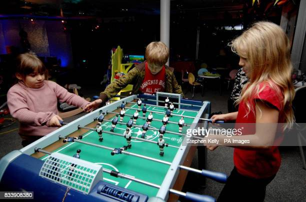 STANDALONE Lucy Felim and Flora play Champions football table with ficroscopic handles at John Lewis in Sloane Square central London