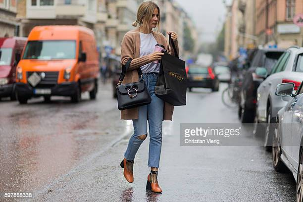 Lucy Williams wearing a beige Filippa K cardigan white thsirt light blue ripped denim jeans JW Anderson bag and socks with fishnet outside Stylein...