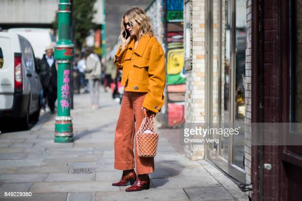 Lucy Williams wearing orange jacket bucket bag outside Marques Almeida during London Fashion Week September 2017 on September 18 2017 in London...
