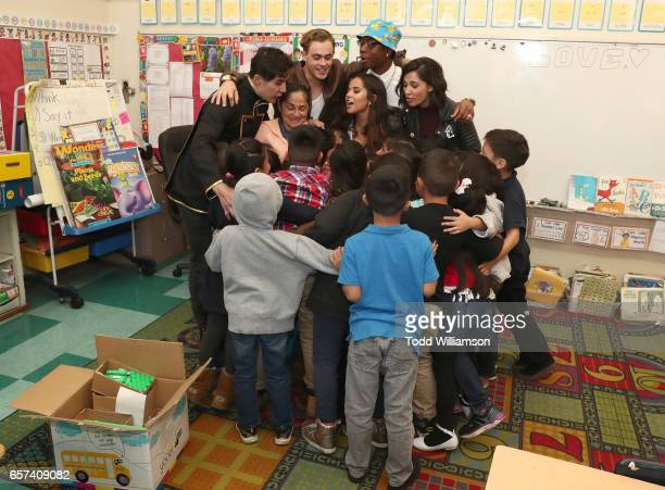 Ludi Lin Dacre Montgomery Becky G RJ Cyler and Naomi Scott group hug with students and their teacher at a Saban's Power Rangers 'Give Day' Event with...