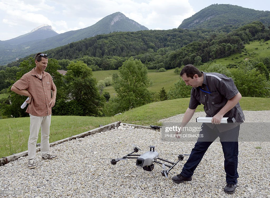 Ludovic Chanut (L), instructor at the Delta drone company teaches to an intern how to pilot a drone during a training session on June 20, 2013 in Quaix-en-Chartreuse near Grenoble, eastern France. Delta drone is one of France's leaders in the drone sector for civil purpose.