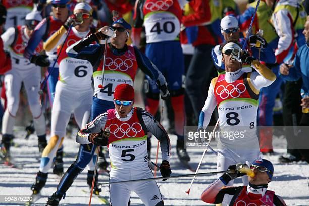 Lufer bei der Verpflegung beim Trinken 50 km Langlauf Massenstart Mnner 50 km men cross skiing mass start olympische Winterspiele in Turin 2006...