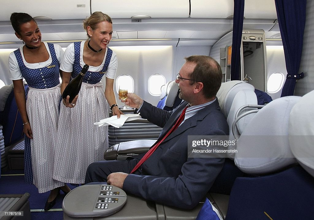 Lufthansa cabin crew members serve drinks during a photocall in traditional 'Blaudruck Dirndl' dress on September 01, 2006 in Munich, Germany. From September 1 to October 3 Lufthansa cabin crew will dress in the Bavarian traditional costume.