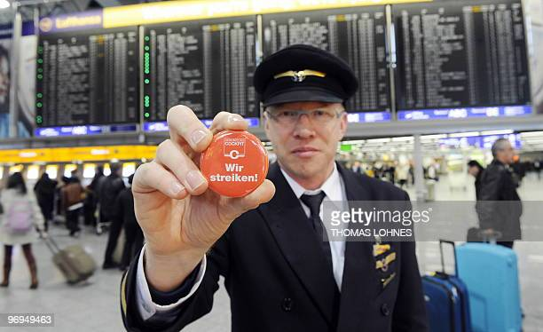 Lufthansa Pilot Ernst van Koert poses for a photo with a badge which reads 'We are on strike' at the airport in the central German city of Frankfurt...