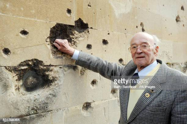 Luftwaffe pilot Willi Schludecker puts a hand into one of the holes caused by bomb damage in the wall of the former Labour Exchange in Bath