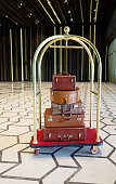 Luggage cart in the lobby of a luxury hotel, brown leather vintage style luggages