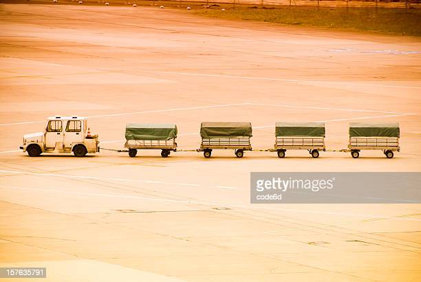 Luggage carts on airport runway at sunset, copy space