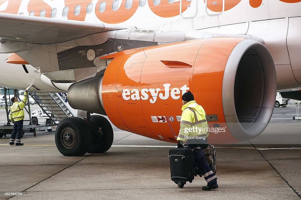 A luggage handler passes a jet engine as he carries passenger's bags to an aircraft, operated by EasyJet Plc, at the airline's hub at London Luton Airport in Luton, U.K., on Tuesday, Nov. 26, 2013. Shares in International Consolidated Airlines Group SA (IAG) and EasyJet Plc climbed at least 2 percent, pushing a gauge of travel and leisure companies higher, as oil prices slid in reaction to Iran's nuclear deal with world powers. Photographer: Simon Dawson/Bloomberg via Getty Images