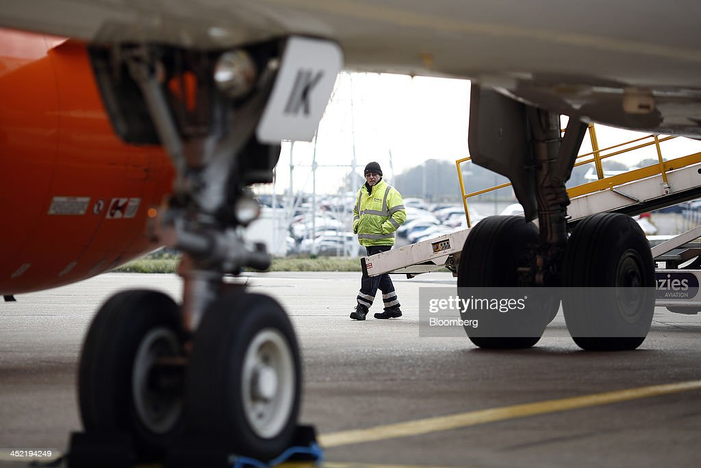 A luggage handler stands near a conveyor belt beside a aircraft, operated by EasyJet Plc, at the airline's hub at London Luton Airport in Luton, U.K., on Tuesday, Nov. 26, 2013. Shares in International Consolidated Airlines Group SA (IAG) and EasyJet Plc climbed at least 2 percent, pushing a gauge of travel and leisure companies higher, as oil prices slid in reaction to Iran's nuclear deal with world powers. Photographer: Simon Dawson/Bloomberg via Getty Images