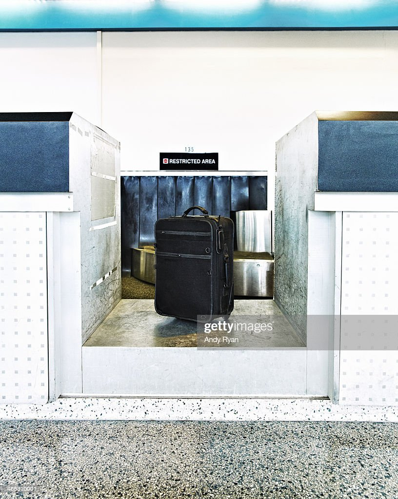 Luggage on scale at airport check-in counter.