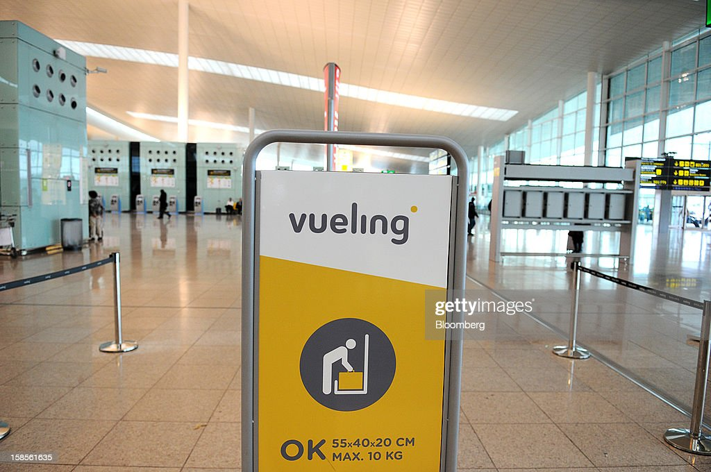 A luggage size restriction sign stands at the Vueling Airlines SA passenger check-in desk at EL Prat airport in Barcelona, Spain, on Wednesday, Dec. 19, 2012. International Consolidated Airlines Group SA won't require European Union approval to buy 100 percent of low-cost carrier Vueling Airlines SA, the EU's antitrust chief said. Photographer: Stefano Buonamici/Bloomberg via Getty Images