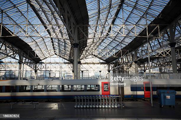 Luggage trolleys sit empty on a platform as a passenger train waits alongside at Waterloo train station in London UK on Monday Oct 28 2013 Millions...