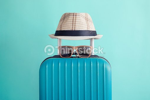 Luggage with woven beach hat and sunglasses on green background minimalistic vacation concept : Stock Photo