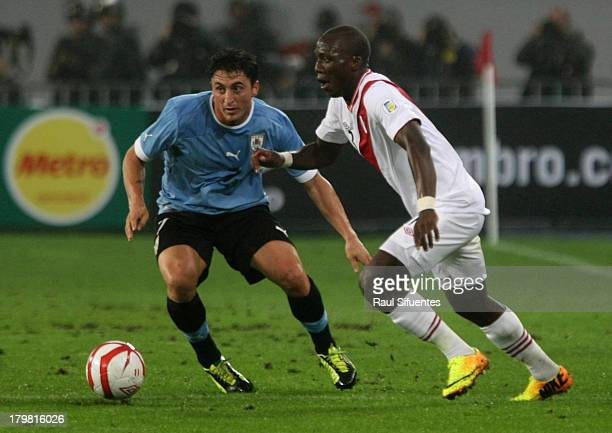 Luis Advincula of Peru fights for the ball with Cristian Rodriguez of Uruguay during a match between Peru and Uruguay as part of the 15th round of...
