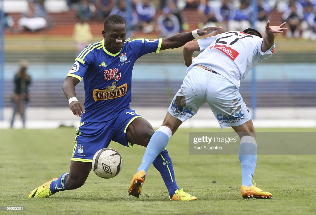 Luis Advincula (L) of Sporting Cristal struggles for the ball with Ivan Santillan (R) of Real Garcilaso during a match between Real Garcilaso and Sporting Cristal as part of the Copa Inca at Municipal de Urcos Stadium on Februay 15, 2014 in Cuzco, Peru.