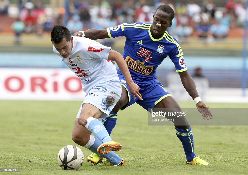 Luis Advincula (R) of Sporting Cristal struggles for the ball with Ivan Santillan (L) of Real Garcilaso during a match between Real Garcilaso and Sporting Cristal as part of the Copa Inca at Municipal de Urcos Stadium on Februay 15, 2014 in Cuzco, Peru.