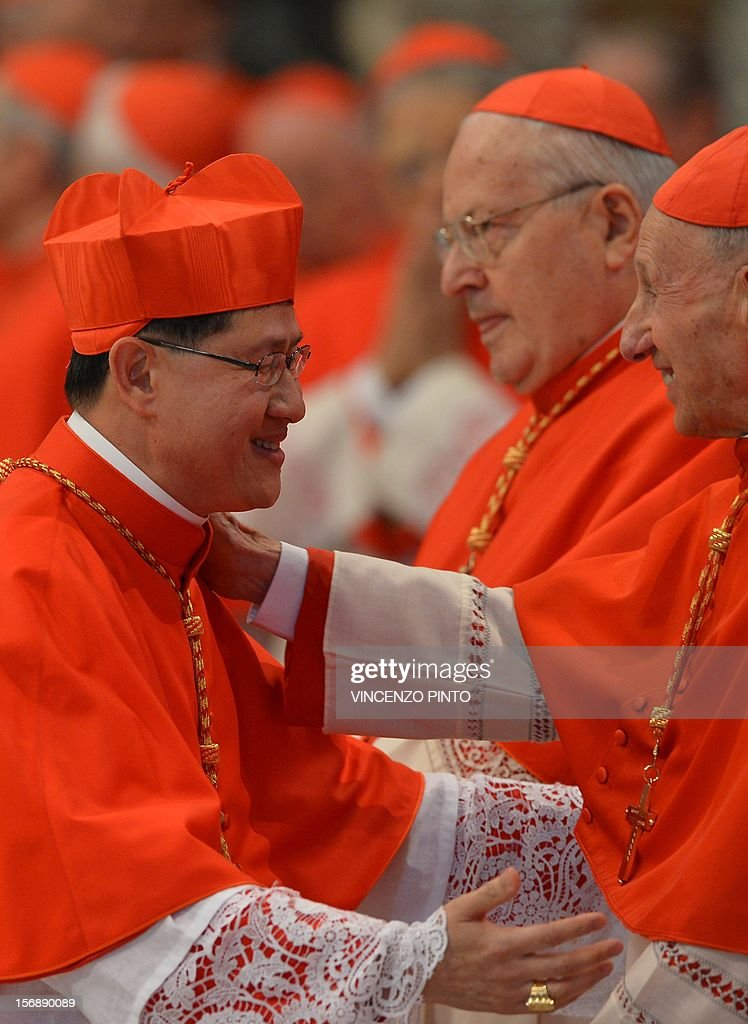 Luis Antonio Tagle of the Philippines wearing his biretta hat is greeted by cardinals after Pope Benedict XVI appointed him as a cardinal during a...