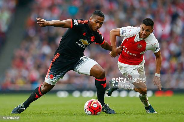 Luis Antonio Valencia of Manchester United is tackled by Alexis Sanchez of Arsenal during the Barclays Premier League match between Arsenal and...