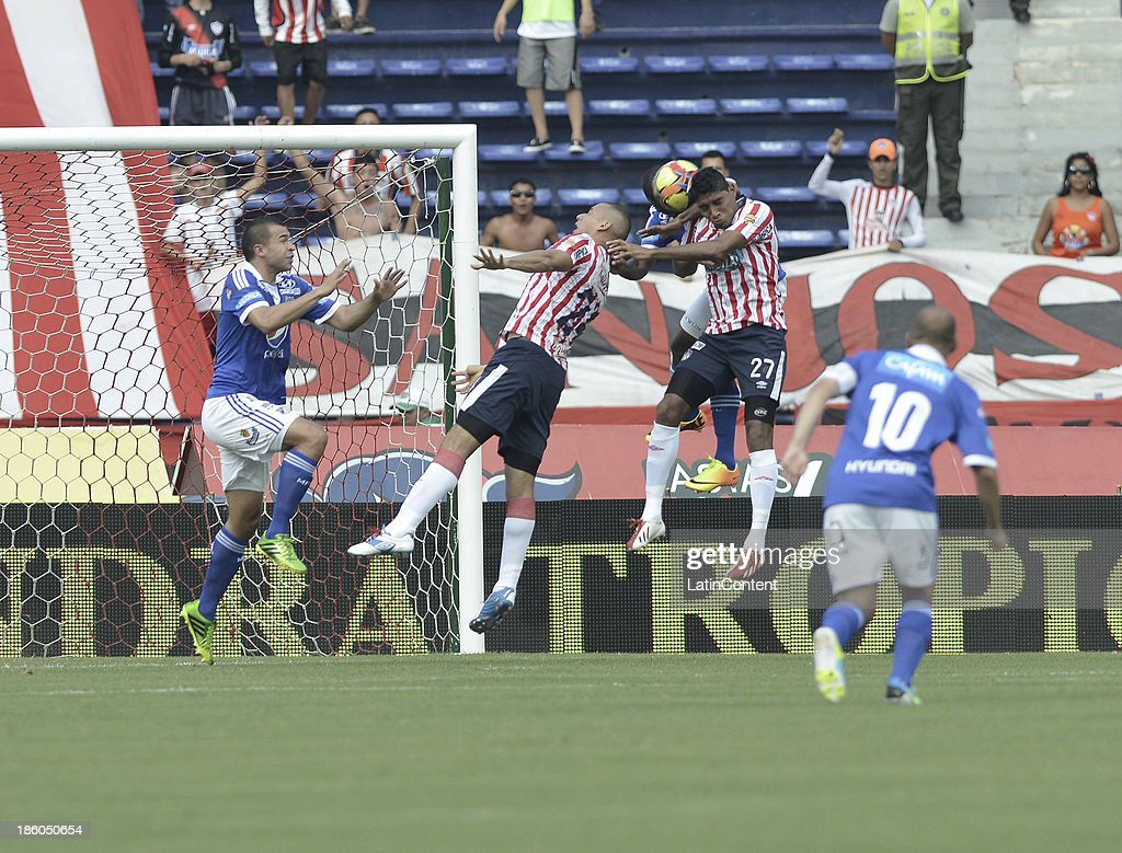 Luis Carlos Ruiz (R) of Junior jumps for the ball with Roman Torres (L) of Millonarios during a match between Atletico Junior and Millonarios as part of the Liga Postobon II 2013 at Metroplitano Roberto Melendez Stadium on October 27, 2013 in Barranquilla, Colombia.
