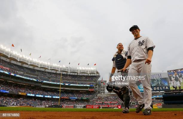 Luis Cessa and catcher Gary Sanchez of the New York Yankees walk to the dugout for a game against the New York Mets at Yankee Stadium on August 14...