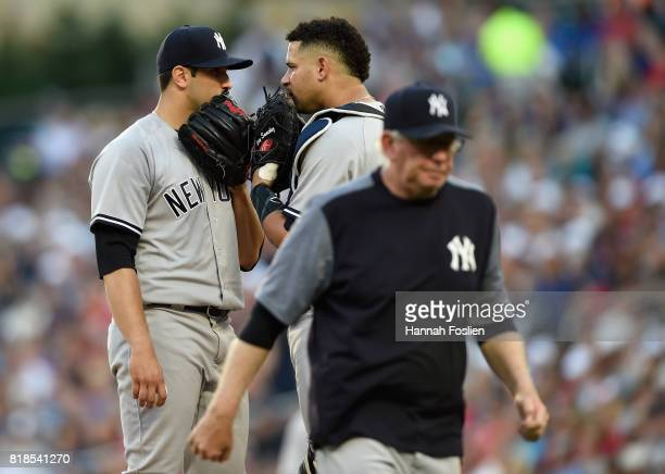 Luis Cessa and Gary Sanchez of the New York Yankees speak on the mound as pitching coach Larry Rothschild returns to the dugout during the first...