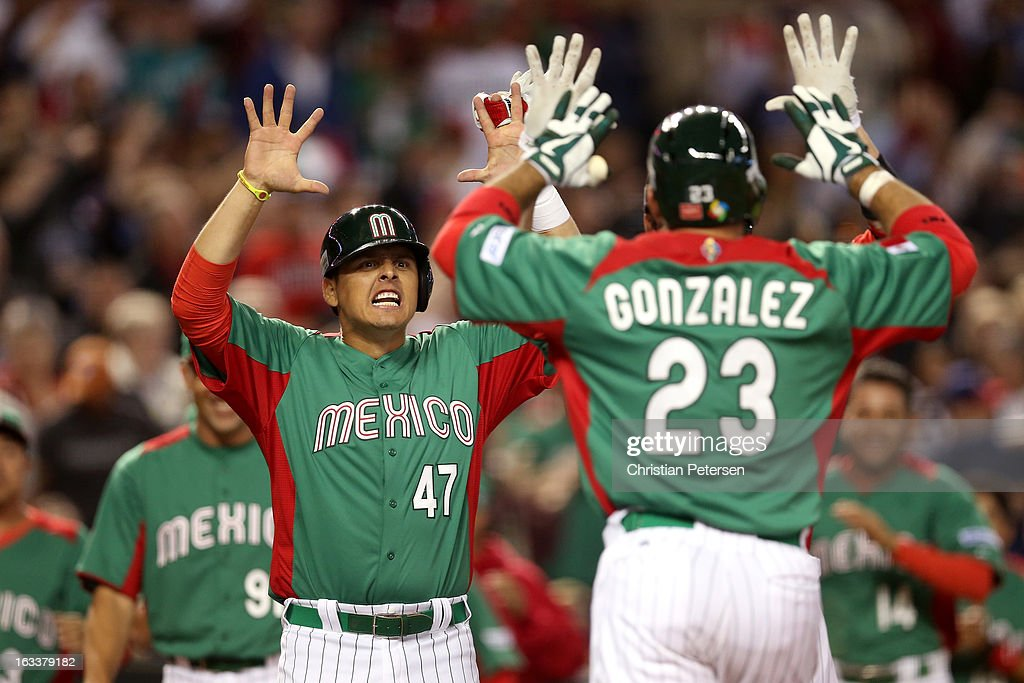 Luis Cruz #47 of Mexico greets teammate Adrian Gonzalez #23 after they both scored on a 2-run home run by Gonzalez in the top of the third inning against the United States during the World Baseball Classic First Round Group D game at Chase Field on March 8, 2013 in Phoenix, Arizona.