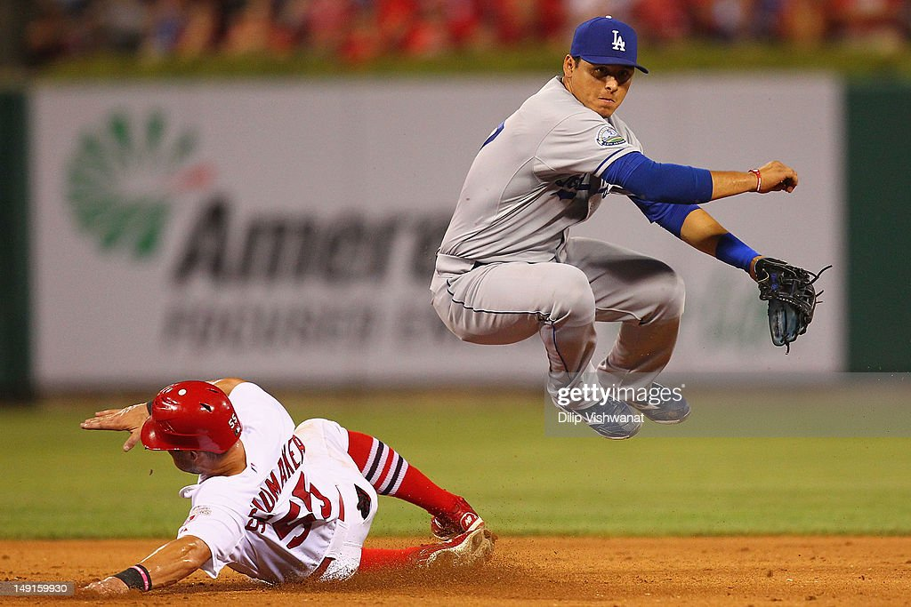 Luis Cruz of the Los Angeles Dodgers turns a double play over Skip Schumaker of the St Louis Cardinals at Busch Stadium on July 23 2012 in St Louis...