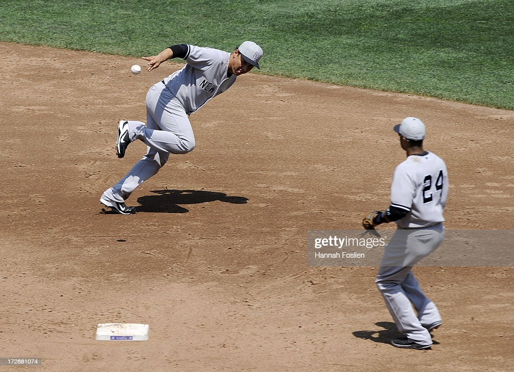 Luis Cruz #61 of the New York Yankees flips the baseball to teammate <a gi-track='captionPersonalityLinkClicked' href=/galleries/search?phrase=Robinson+Cano&family=editorial&specificpeople=538362 ng-click='$event.stopPropagation()'>Robinson Cano</a> #24 to start a double play against the Minnesota Twins during the third inning of the game on July 4, 2013 at Target Field in Minneapolis, Minnesota.