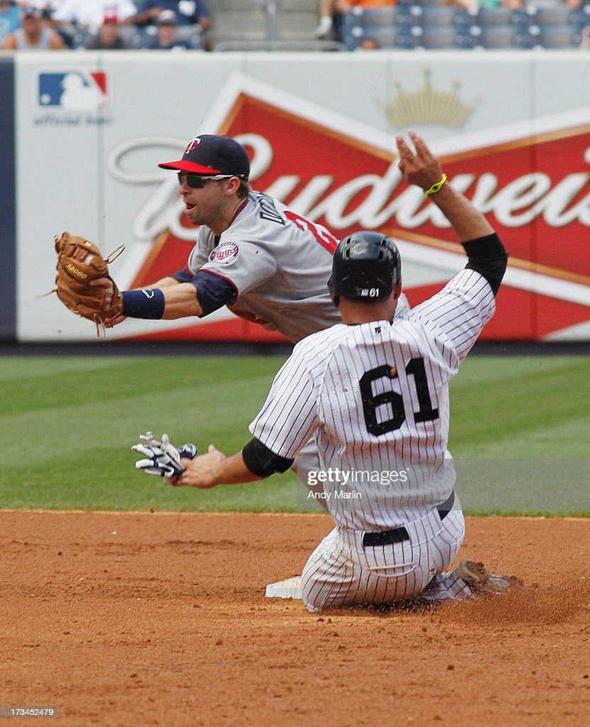 Luis Cruz #61 of the New York Yankees is forced out at second base in the bottom of the fourth inning by <a gi-track='captionPersonalityLinkClicked' href=/galleries/search?phrase=Brian+Dozier&family=editorial&specificpeople=7553002 ng-click='$event.stopPropagation()'>Brian Dozier</a> #2 of the Minnesota Twins at Yankee Stadium on July 14, 2013 in the Bronx borough of New York City. The Twins defeated the Yankees 10-4.