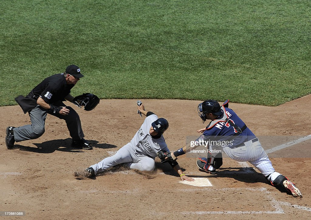 Luis Cruz #61 of the New York Yankees is out as <a gi-track='captionPersonalityLinkClicked' href=/galleries/search?phrase=Joe+Mauer&family=editorial&specificpeople=214614 ng-click='$event.stopPropagation()'>Joe Mauer</a> #7 of the Minnesota Twins defends home plate and umpire Ed Hickox #15 looks on during the sixth inning of the game on July 4, 2013 at Target Field in Minneapolis, Minnesota.