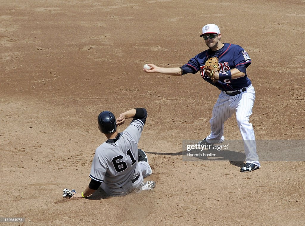 Luis Cruz #61 of the New York Yankees is out at second base as <a gi-track='captionPersonalityLinkClicked' href=/galleries/search?phrase=Brian+Dozier&family=editorial&specificpeople=7553002 ng-click='$event.stopPropagation()'>Brian Dozier</a> #2 of the Minnesota Twins turns a double play during the third inning of the game on July 4, 2013 at Target Field in Minneapolis, Minnesota.