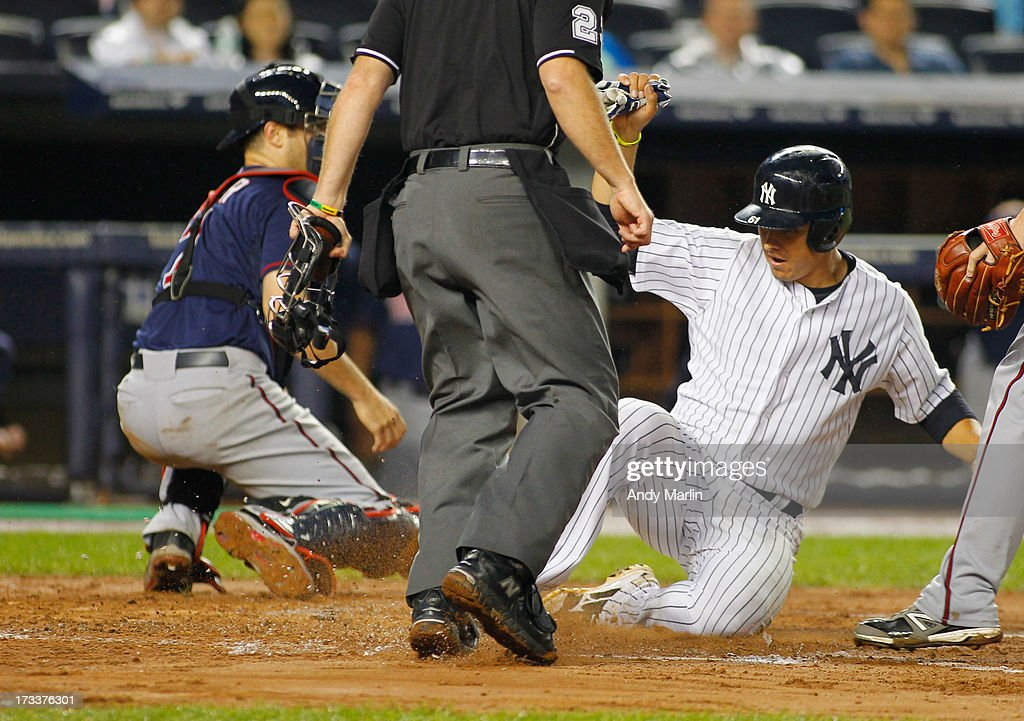 Luis Cruz #61 of the New York Yankees slides home for the go ahead run on a single by <a gi-track='captionPersonalityLinkClicked' href=/galleries/search?phrase=Brett+Gardner&family=editorial&specificpeople=4172518 ng-click='$event.stopPropagation()'>Brett Gardner</a> #11 (not pictured) in the bottom of the fifth inning against the Minnesota Twins at Yankee Stadium on July 12, 2013 in the Bronx borough of New York City.