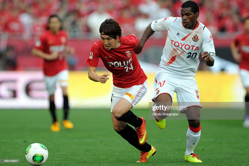 Luis Danilson Cordoba Rodrigues of Nagoya Grampus and Genki Haraguchi of Urawa Red Diamonds compete for the ball during the J.League match between Urawa Red Diamonds and Nagoya Grampus at Saitama Stadium on March 9, 2013 in Saitama, Japan.