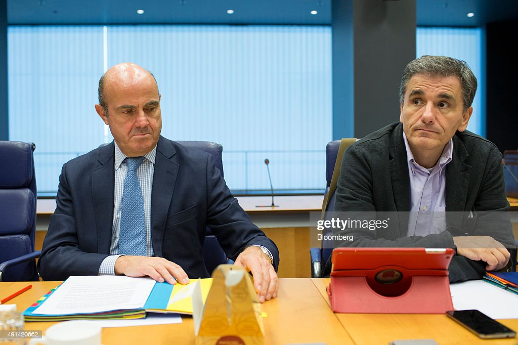 Luis de Guindos, Spain's economy minister, left, sits beside Euclid Tsakalotos, Greece's finance minister, ahead of roundtable talks during a Eurogroup meeting in Luxembourg, on Monday, Oct. 5, 2015. French Finance Minister Michel Sapin said Greece needs to make good on its promises with euro-area lenders as soon as possible so the creditors can move on to discuss easing the country's debt burden. Photographer: Jasper Juinen/Bloomberg via Getty Images