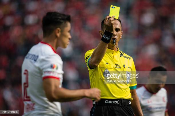Luis Enrique Santander central referee shows a yellow card to Efrain Velarde of Toluca during the 4th round match between Cruz Azul and Chivas as...